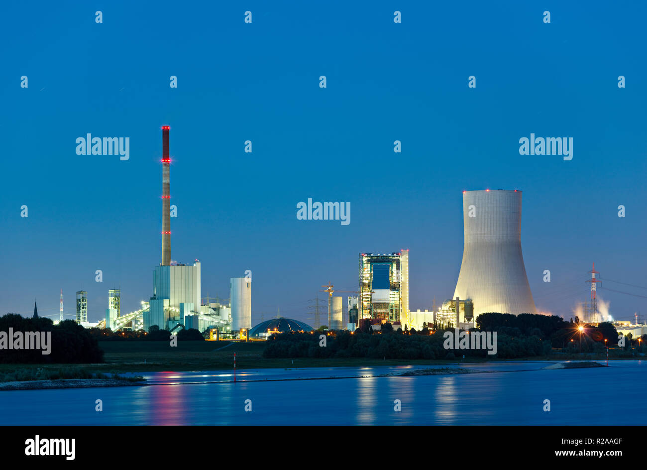 Old and new coal power stations side by side with reflection in the water and night blue sky. The new cooling tower has a height of 180m which makes i - Stock Image