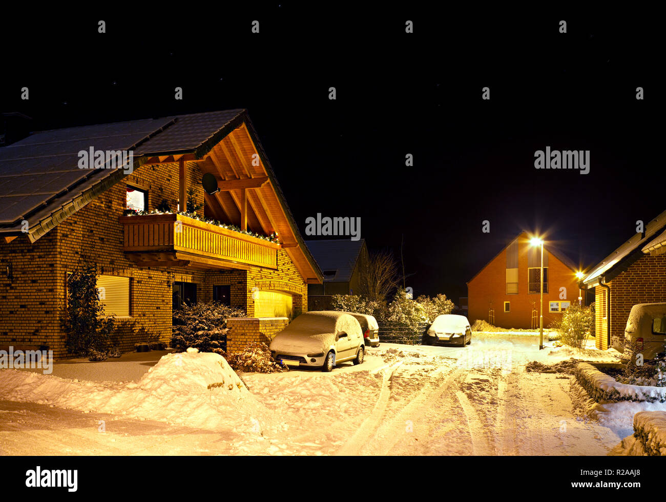 Night shot of a little street after a snow fall during christmas time. - Stock Image