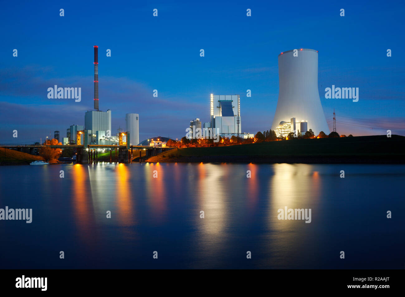 An old and a new coal power station side by side with reflection in the water and night blue sky. - Stock Image