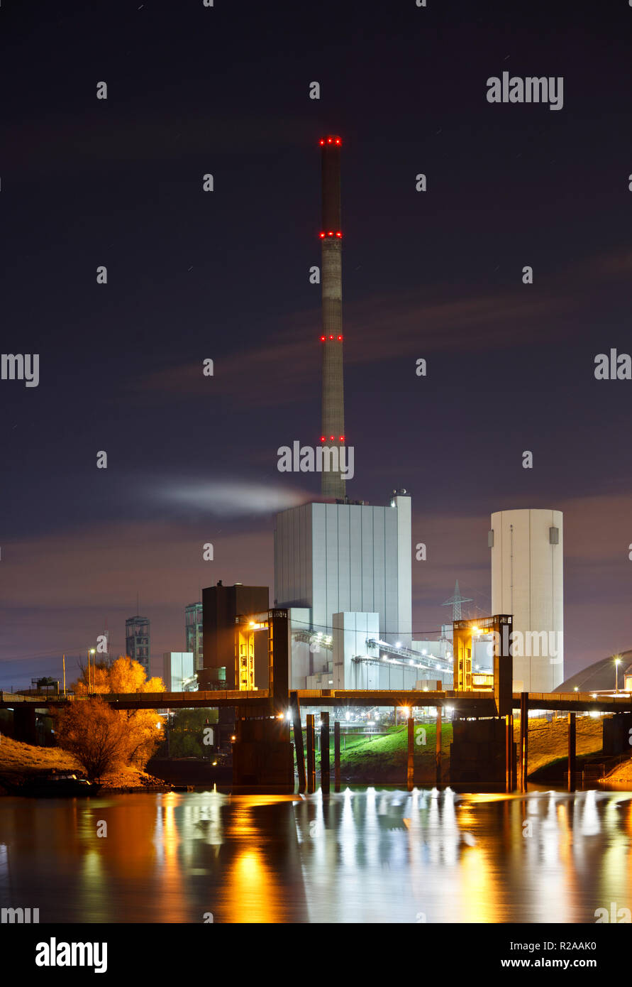 An old coal power station with reflection in the water at night, a bridge in front. - Stock Image