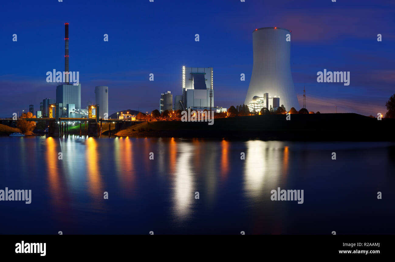 Nightly panorama of an old and a new coal power station side by side with reflection in the water and night blue sky. - Stock Image