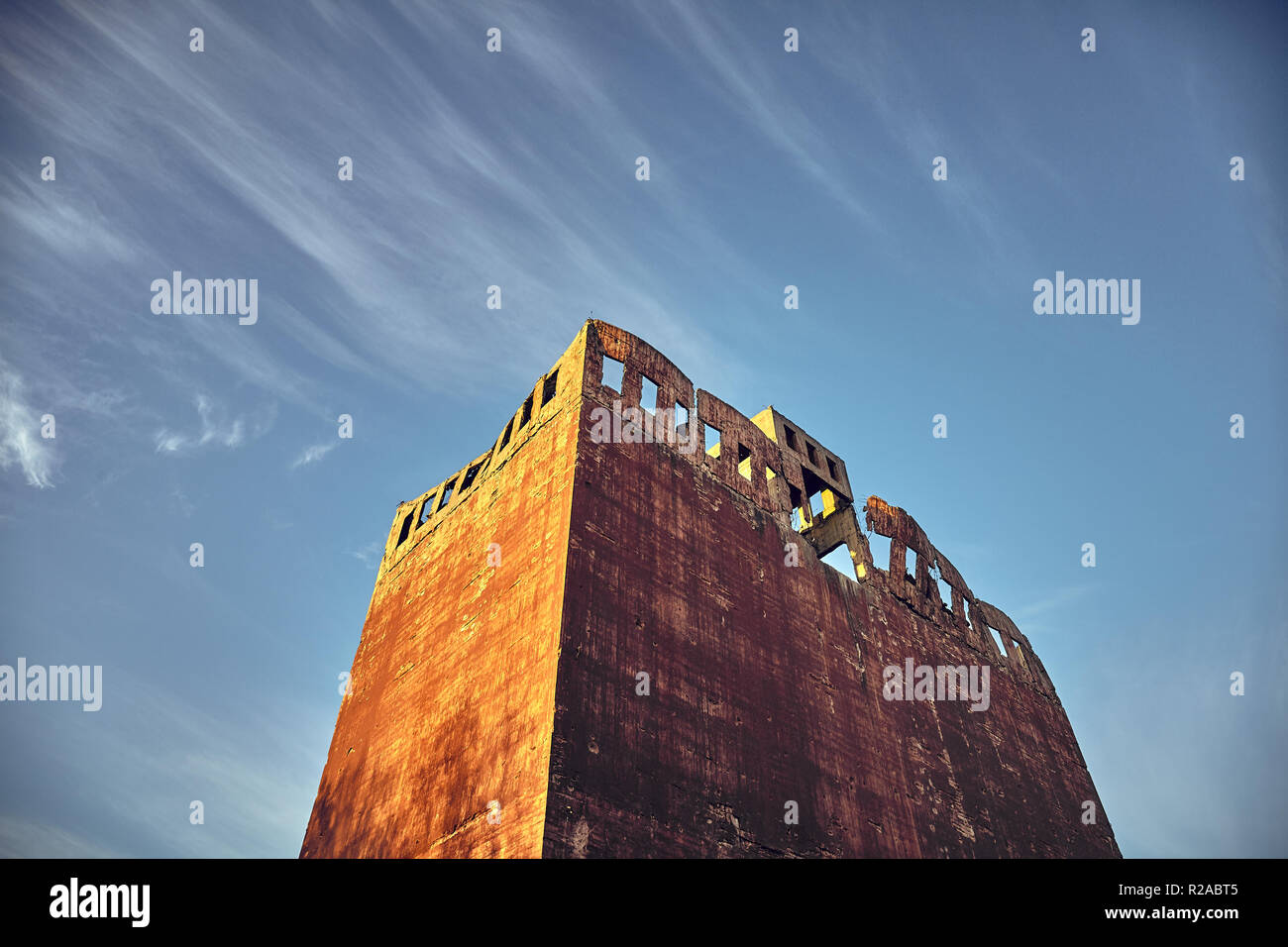 Scary abandoned post apocalyptic style concrete tower at sunset, color toned picture. - Stock Image