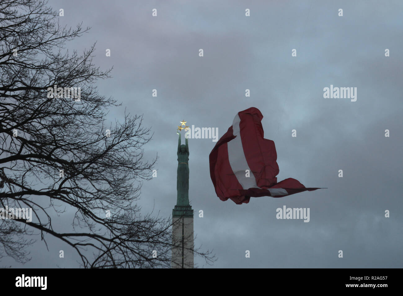 Riga, Latvia. 18th Nov, 2018. A Latvian flag is flying at the Freedom Monument. Latvia celebrates its 100th birthday with numerous events. Exactly a century ago - on 18 November 1918 - the Baltic State proclaimed its independence from Russia. Credit: Alexander Welscher/dpa/Alamy Live News - Stock Image