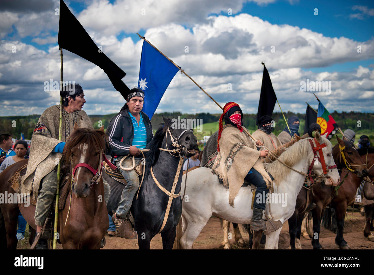17 November 2018, Chile, Temucuicui: 'Weichafe', fighters from the indigenous Mapuche people, on horseback, take part in the funeral of 24-year-old Camilo Catrillanca in a cemetery. A special unit of the Chilean military police (Carabineros) had shot Catrillanca on 14.11.2018 in the indigenous Mapuche community Temucuicui. According to police, the officers tracked three car thieves who had stolen their teachers' vehicles. The persecution led them into the territory of the Mapuche community of Temucuicui. Following Catrillanca's death, Mapuche organisations have called for protests across the c - Stock Image