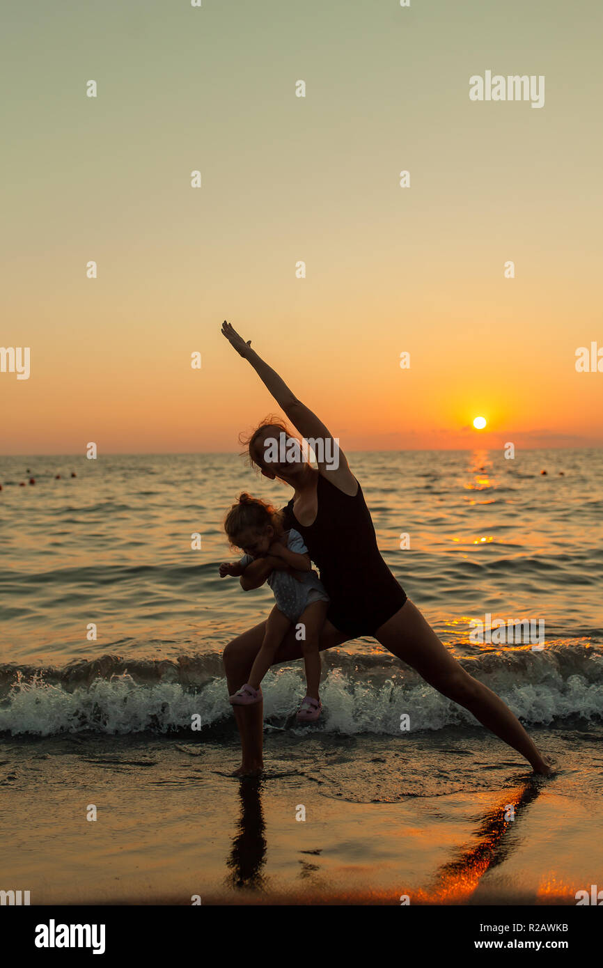 woman and girl silhouette practicing balancing yoga warrior pose together during ocean sunset with bright orange sky and water reflections. - Stock Image