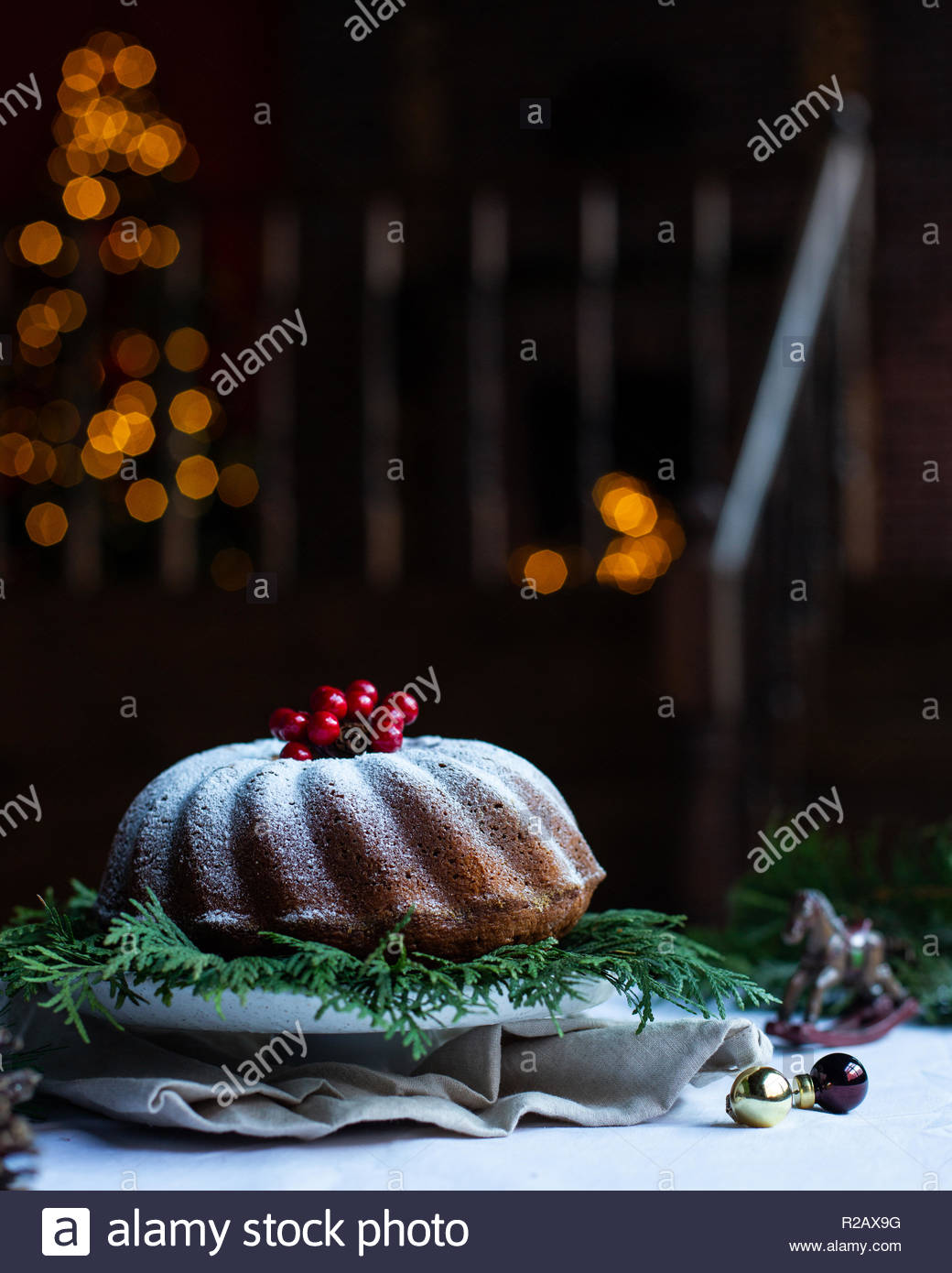Dark cozy room with a staircase and Christmas decorations. Christmas lights in bokeh. Fireplace and Christmas tree on background. - Stock Image