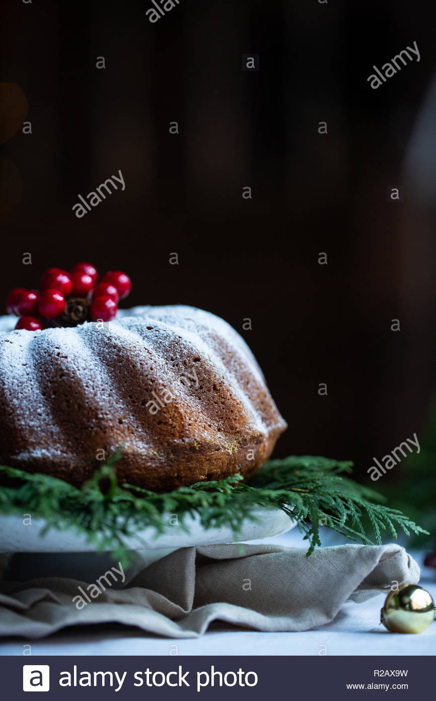 White table serving with vintage white crockery. Fresh cake with sugar powder on white stand and juniper twigs. Rustic style wooden room. - Stock Image