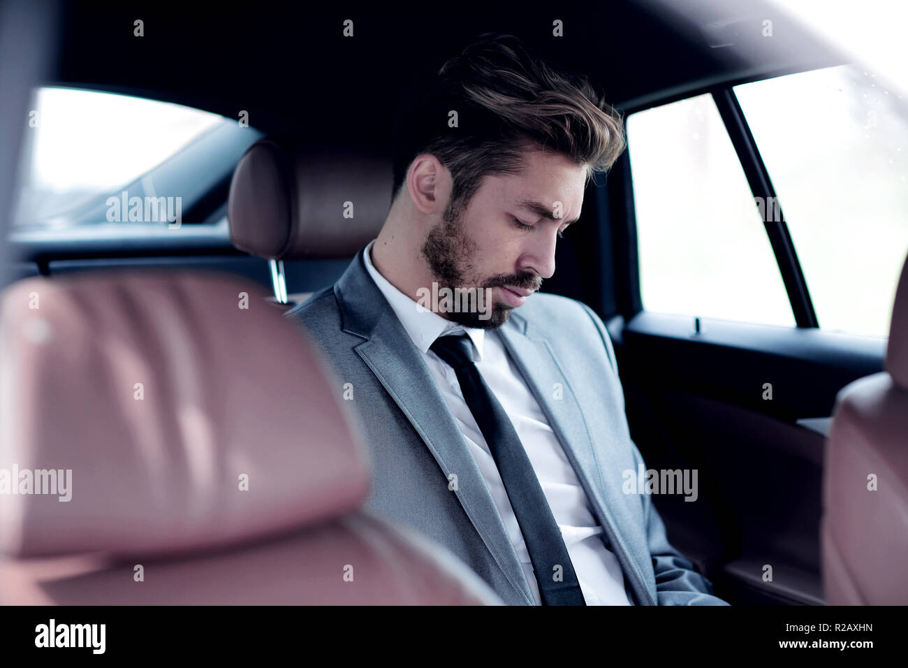 Unsmiling businessman sitting in the back seat in his car - Stock Image