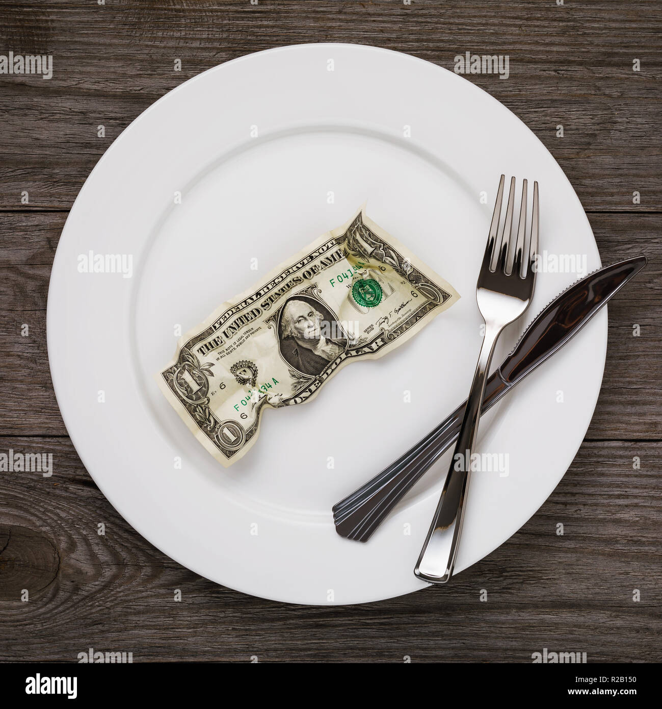 Crumpled dollar in the plate with fork and knife on the wooden table. Concept on the subject of human needs - Stock Image