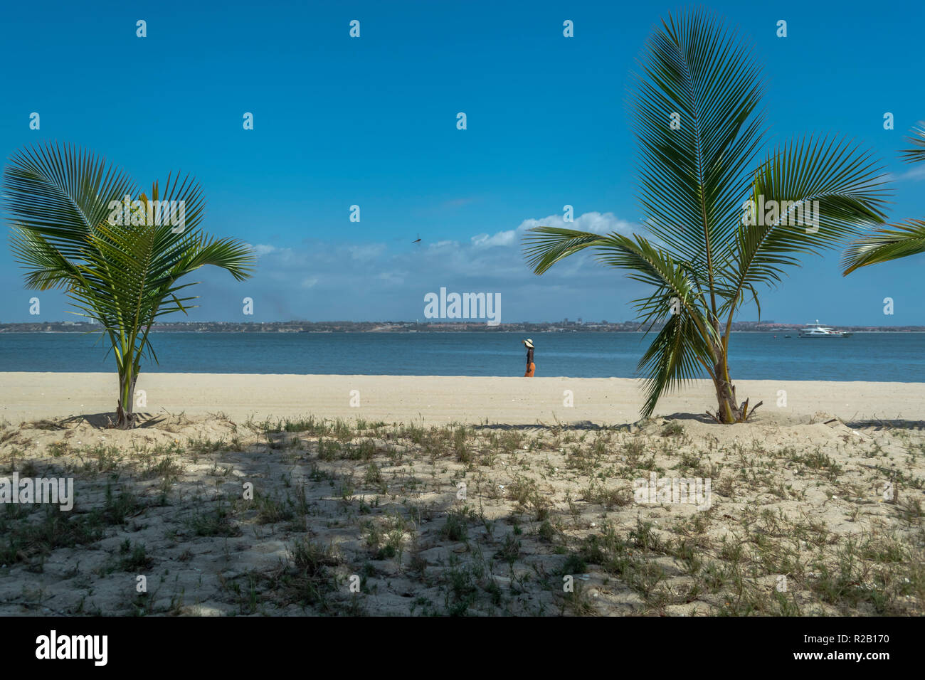 View of palm trees and a woman on beach, and boats on water, on the island of Mussulo, Luanda, Angola... - Stock Image