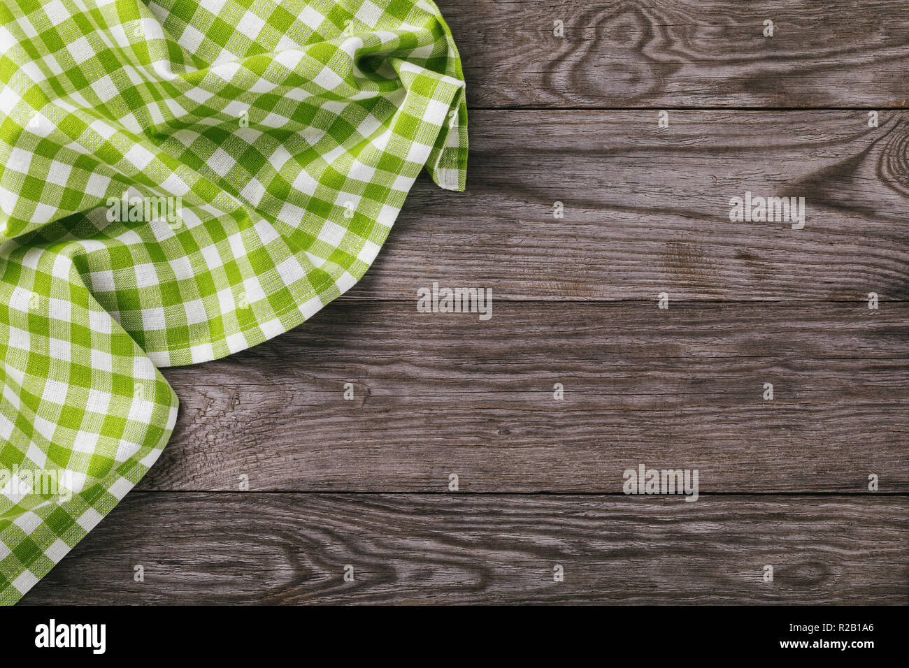 Top view on a multi-colored napkin on the left side of a wooden table with copy space - Stock Image