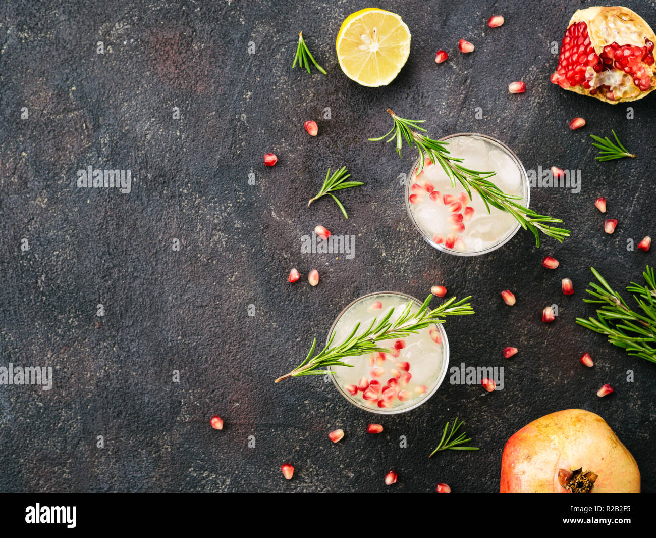 Autumn and winter cocktails idea - white sangria with rosemary, pomegrante and lemon juice and ingredients on black cement background. Copy space. Top view or flat-lay. - Stock Image