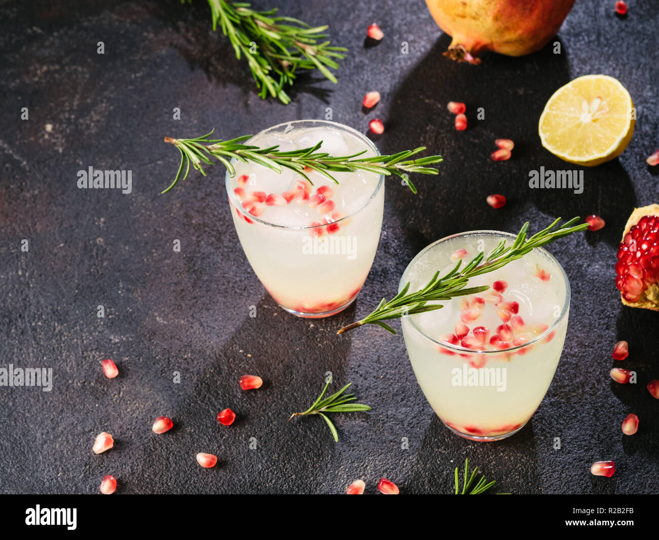 Autumn and winter cocktails idea - white sangria with rosemary, pomegrante and lemon juice and ingredients on black cement background. Copy space. - Stock Image