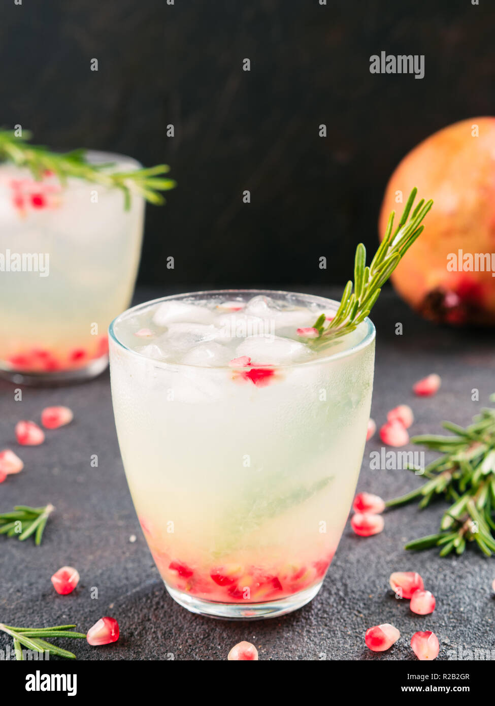 Autumn and winter cocktails idea - white sangria with rosemary, pomegrante and lemon juice and ingredients on black cement background. - Stock Image