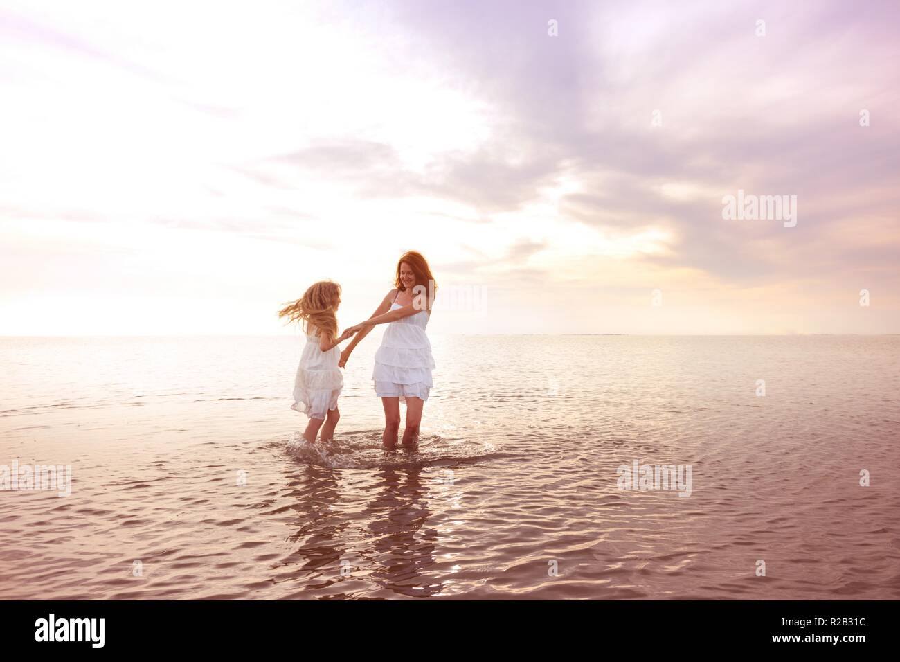 happy fun weekend by the sea - Mom and daughter in white dresses whirling by the sea at sunset. Ukrainian landscape at the Sea of Azov, Ukraine - Stock Image