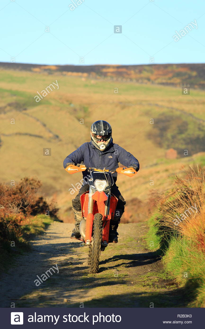 A man riding a dirt bike in open countryside. Mossley UK Autumn Late Afternoon November 2018 - Stock Image