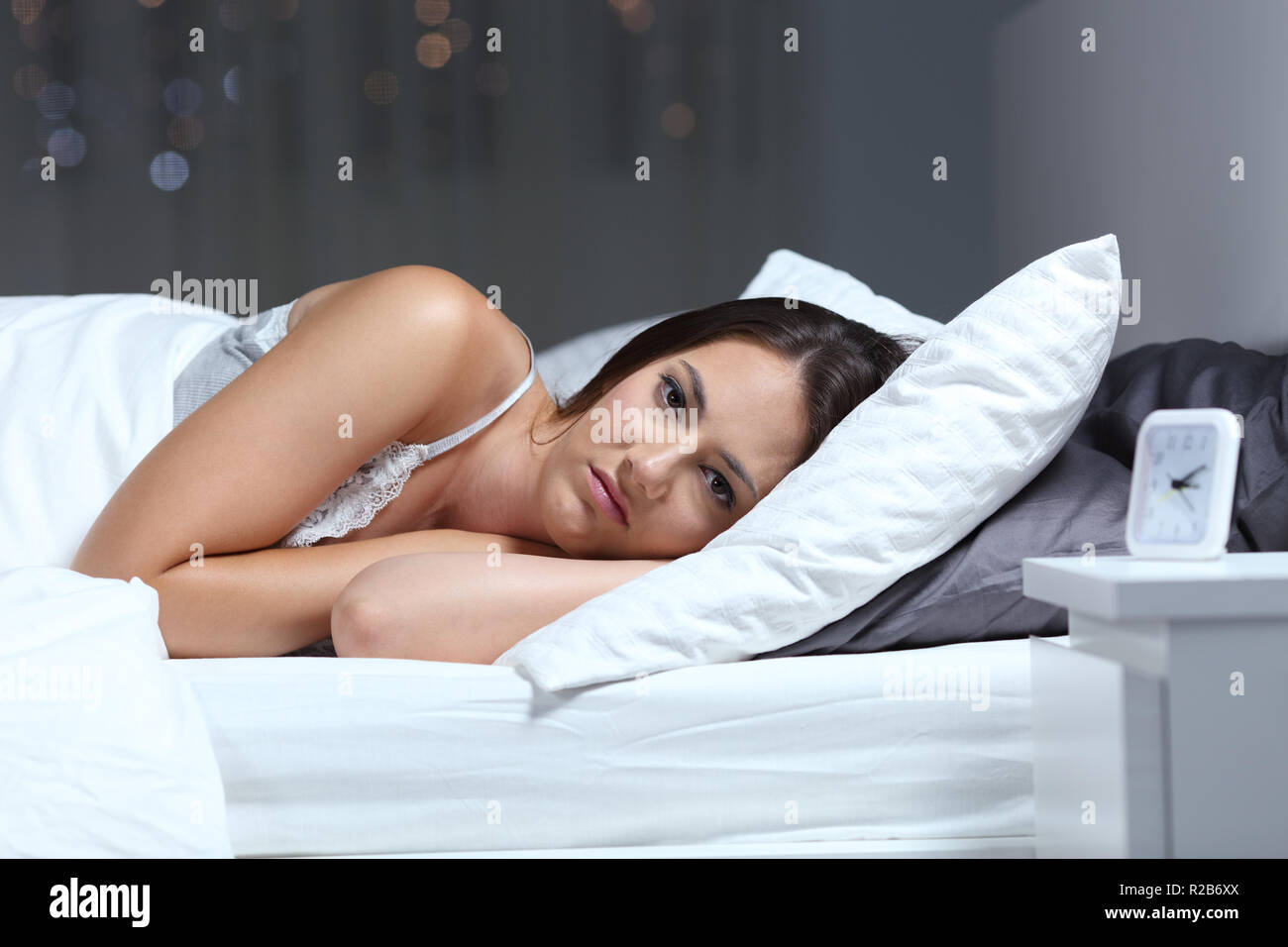 Angry insomniac woman looking at camera lying on a bed in the night at home - Stock Image