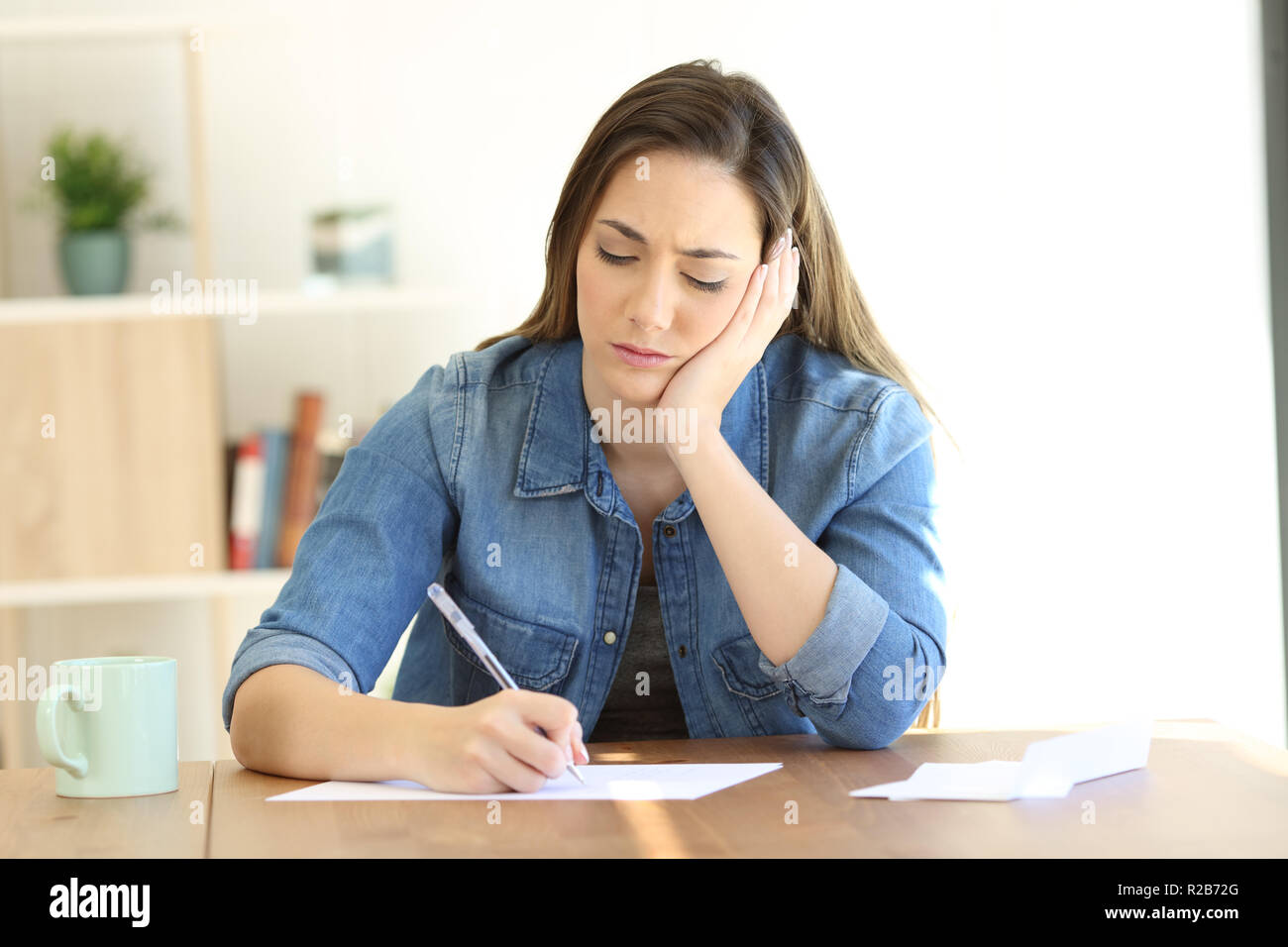 Front view of a worried woman writing notes or a letter at home - Stock Image