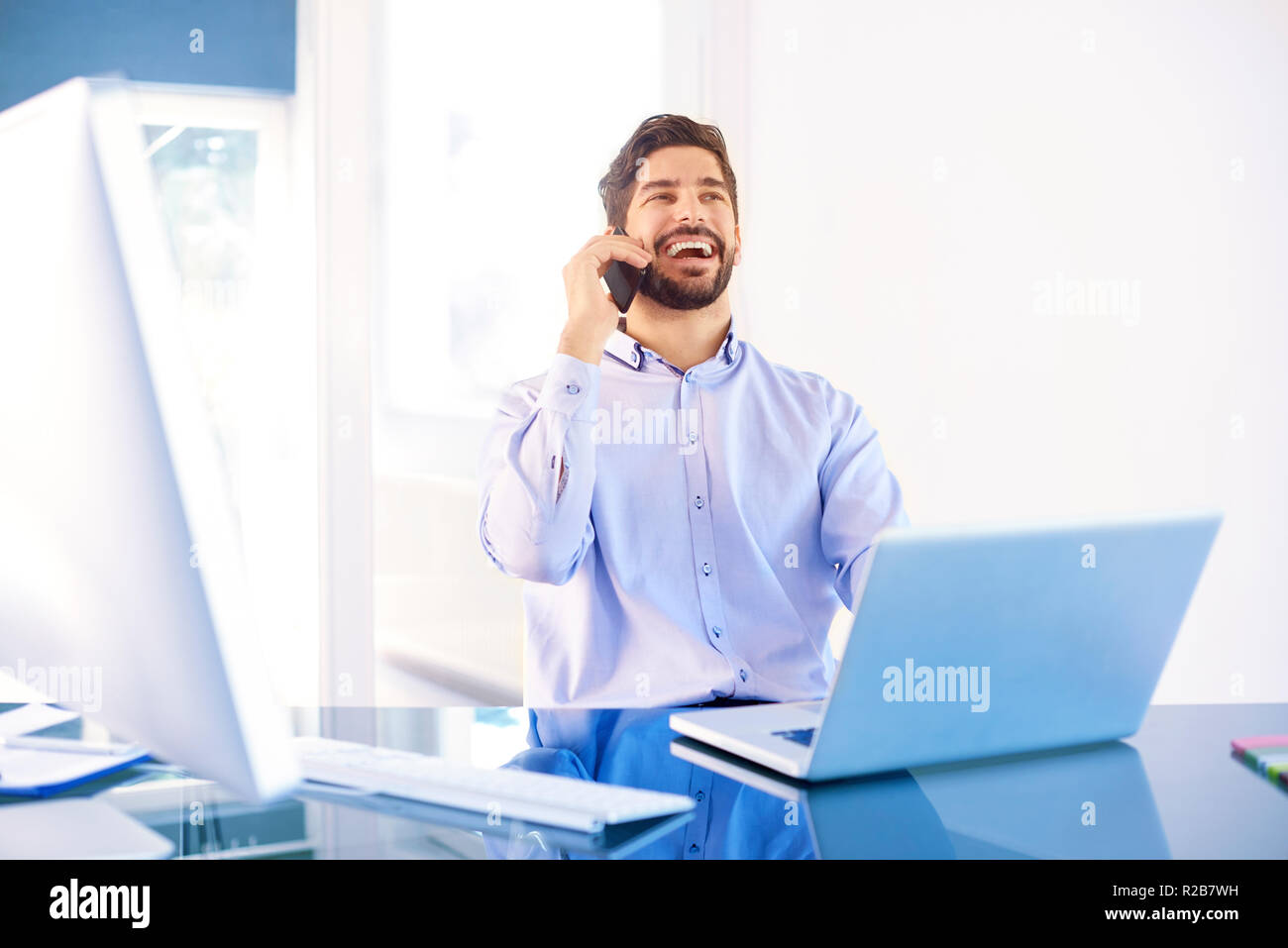 Happy Businessman Wearing Shirt While Sitting At Office Desk
