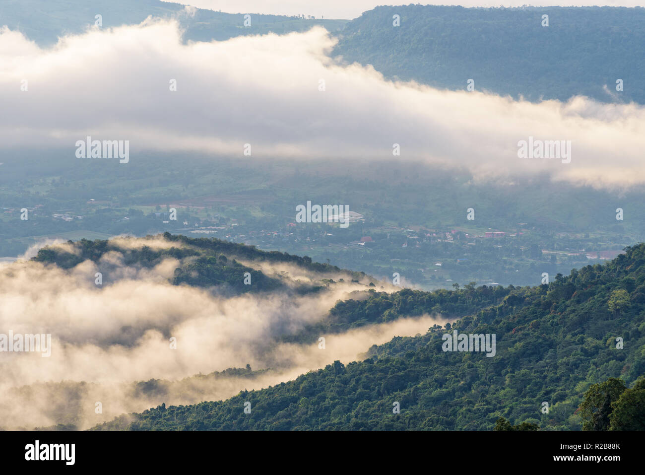 Beautiful nature landscape clouds and fogs like the sea is covered peaks in winter morning during sunrise at viewpoint of Phu Ruea National Park, Loei - Stock Image
