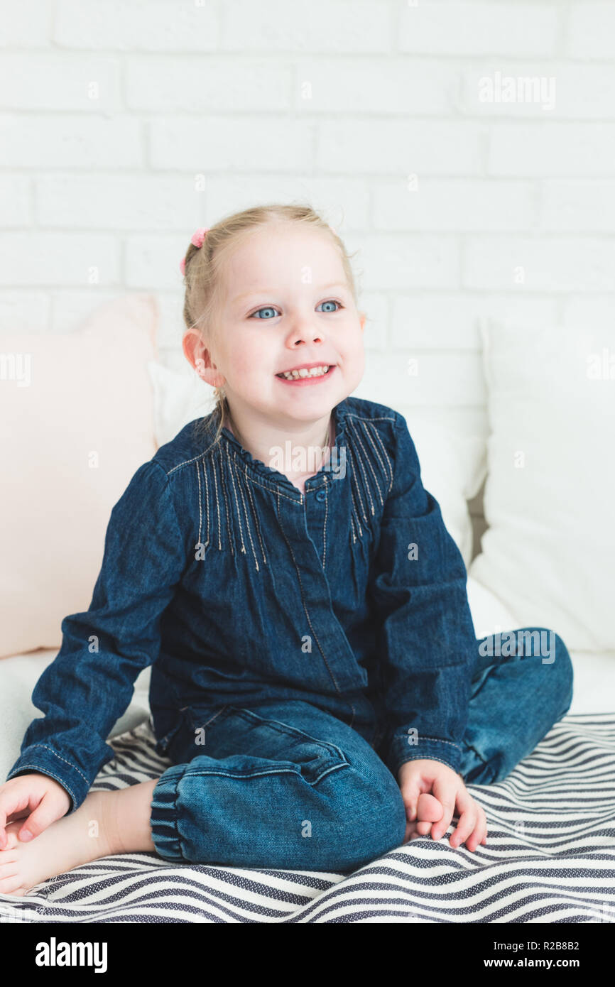 Cute little girl in blue denim overalls sitting on the bed. - Stock Image
