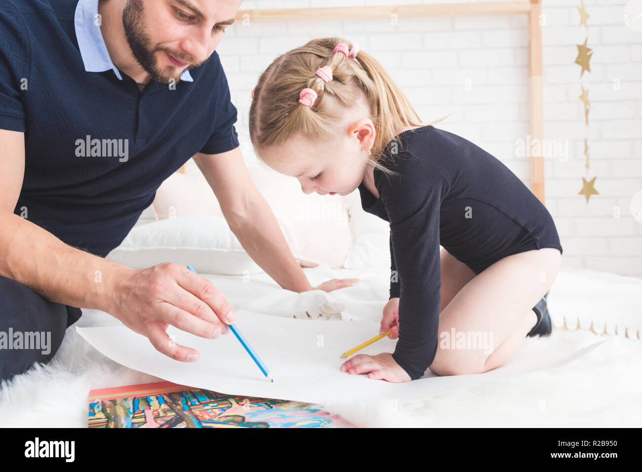 A young father and his daughter lie on the floor and draw with colored pencils. - Stock Image