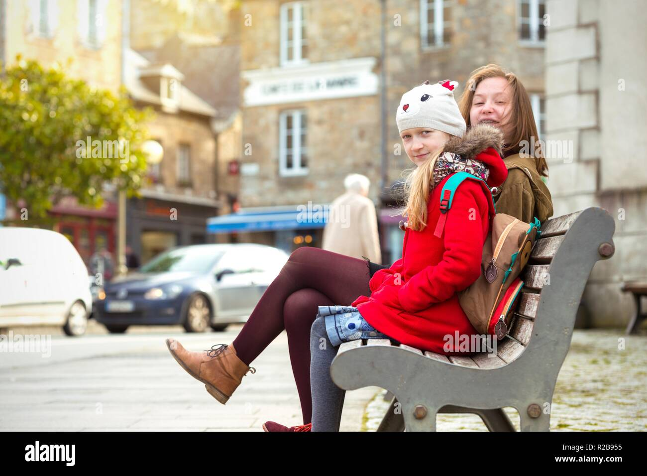 the sisters are sitting on the bench in the famous city of Dinan. France. - Stock Image