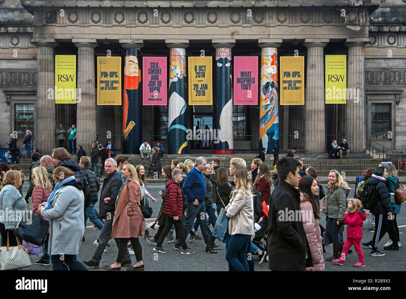 Pedestrians walking along Princes Street in front of the RSA Building advertising 'Pin-Ups   Toulouse-Lautrec and the Art of Celebrity' . - Stock Image