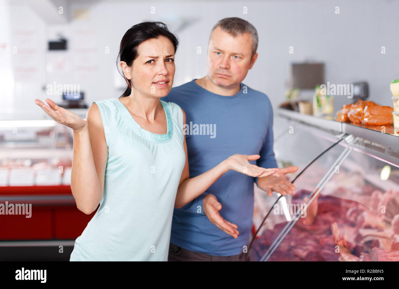 Sad adult couple customers choosing meat in butcher's shop - Stock Image