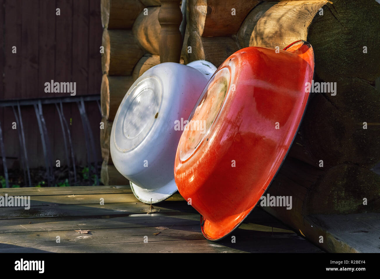 Two enameled household basins, standing on the wooden floor and leaning against the wall of logs. - Stock Image