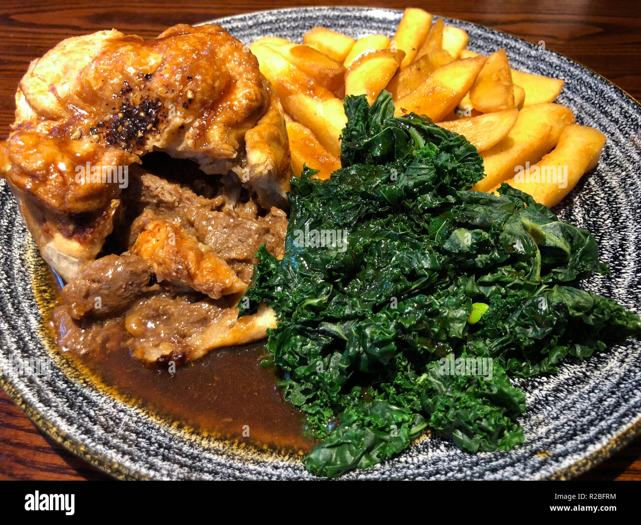 Steak pie with chips, cabbage and gravy - Stock Image