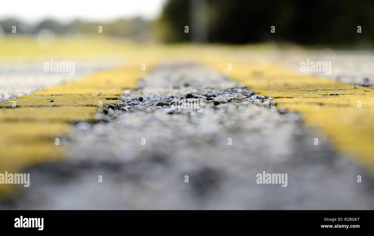 Space between yellow divider lines on a road in Texas; low perspective and vanishing focal point. - Stock Image