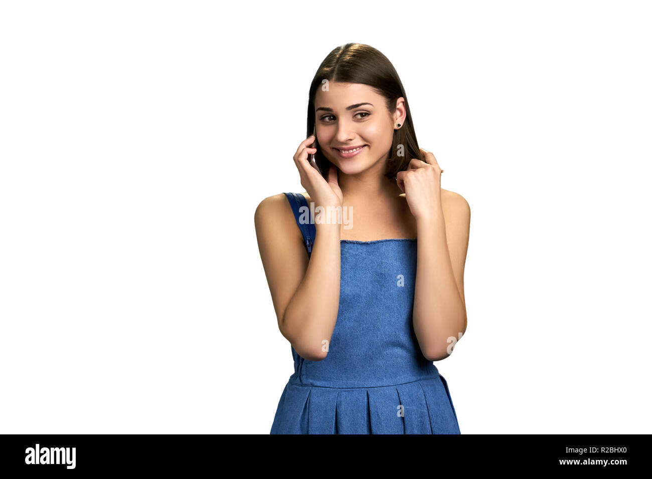 7c71a1ac76dd Young coquette woman talking on phone. Pretty girl speaking on phone with  guy, isolated on white background. Attractive brunette with phone.