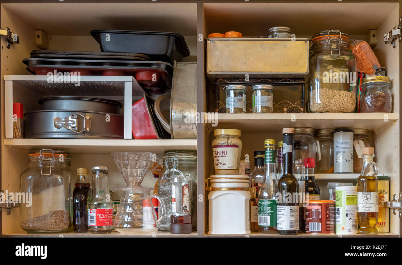 Domestic kitchen cupboards interior with stored ingredients, baking tins, coffee jugs, and food. - Stock Image