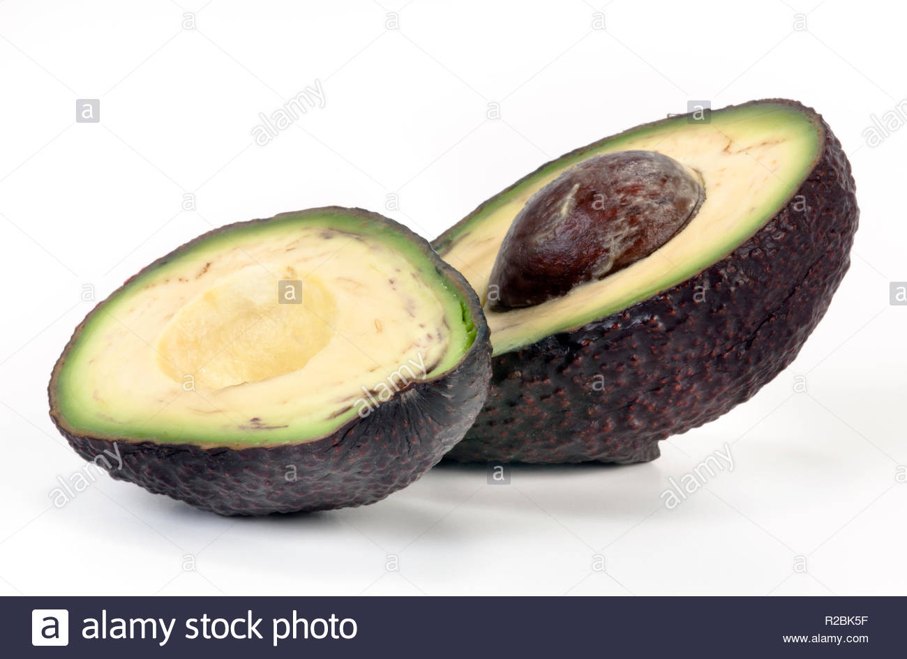 Halved Avocado with pip isolated on white background. Stock Photo