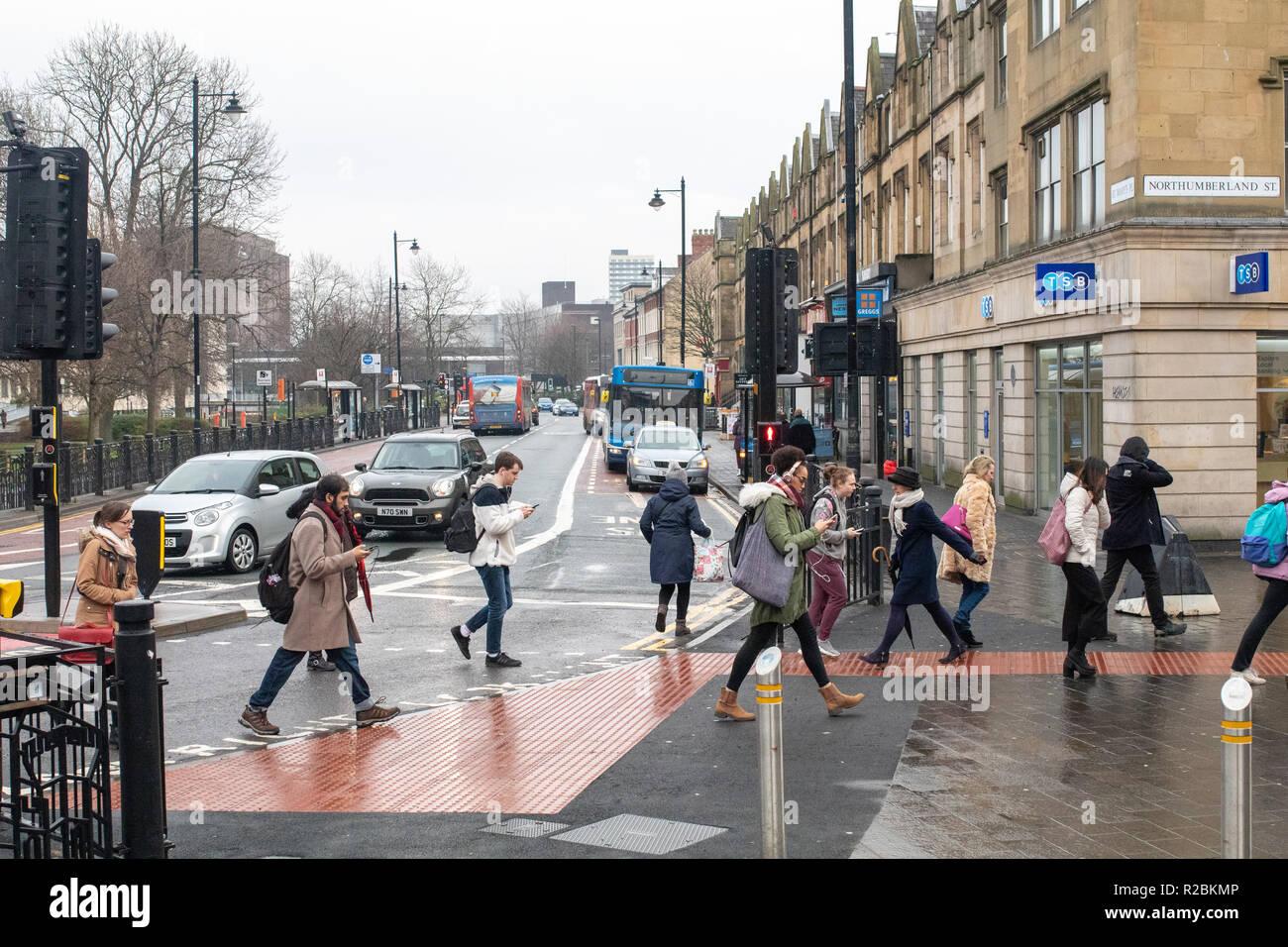 Newcastle upon Tyne/England - January 10th 2018: Newcastle people walking across busy street on mobile phones - Stock Image