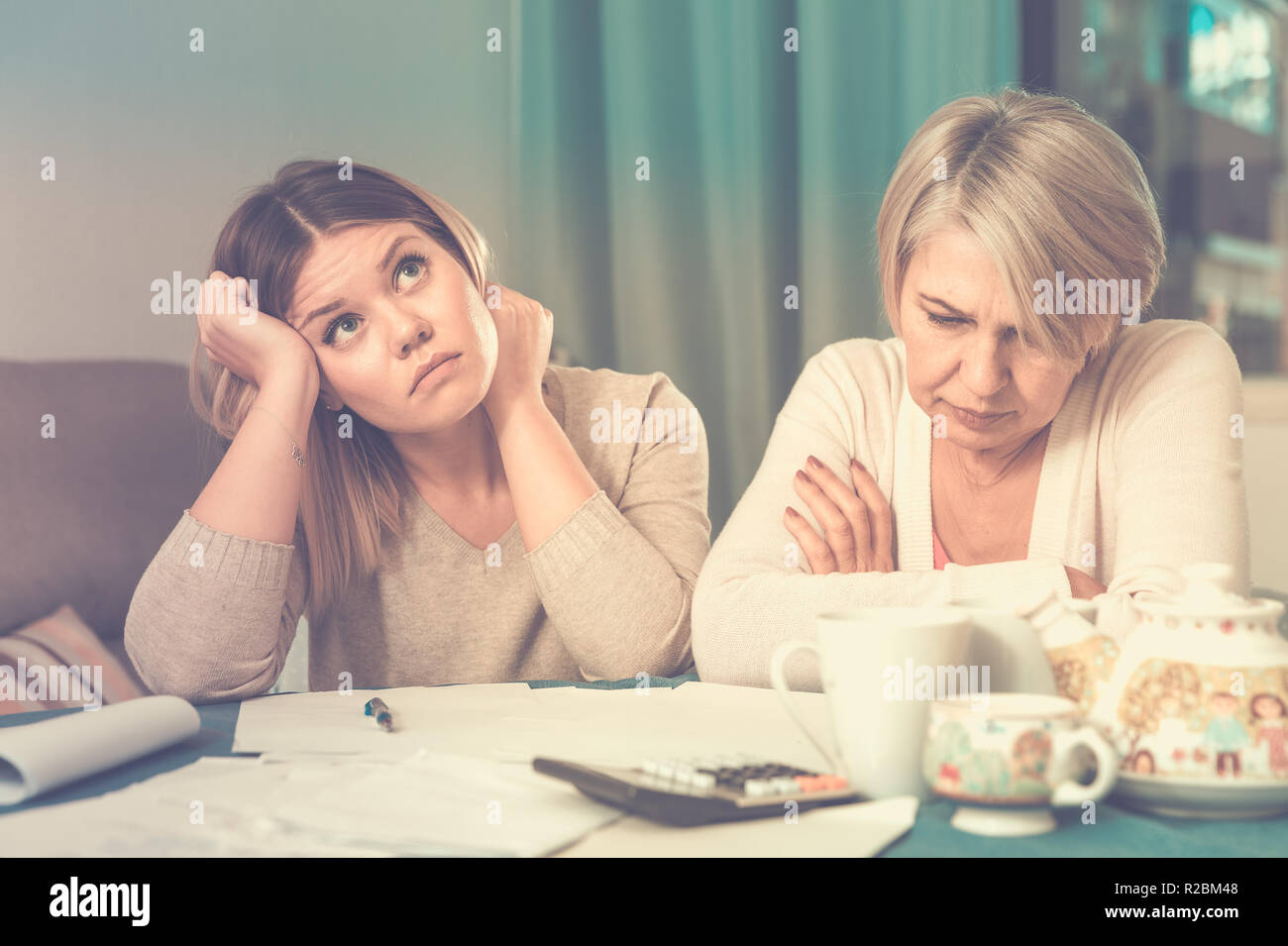 Financial problems cast disheartened mother and her adult daughter - Stock Image
