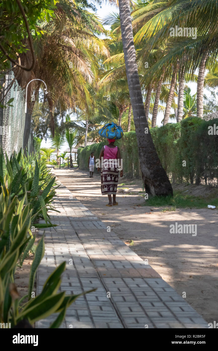 Mussulo/Luanda/Angola - 11/11/2018:View of pedestrian path, with woman selling street walking and also a man, in Mussulo island, Angola - Stock Image