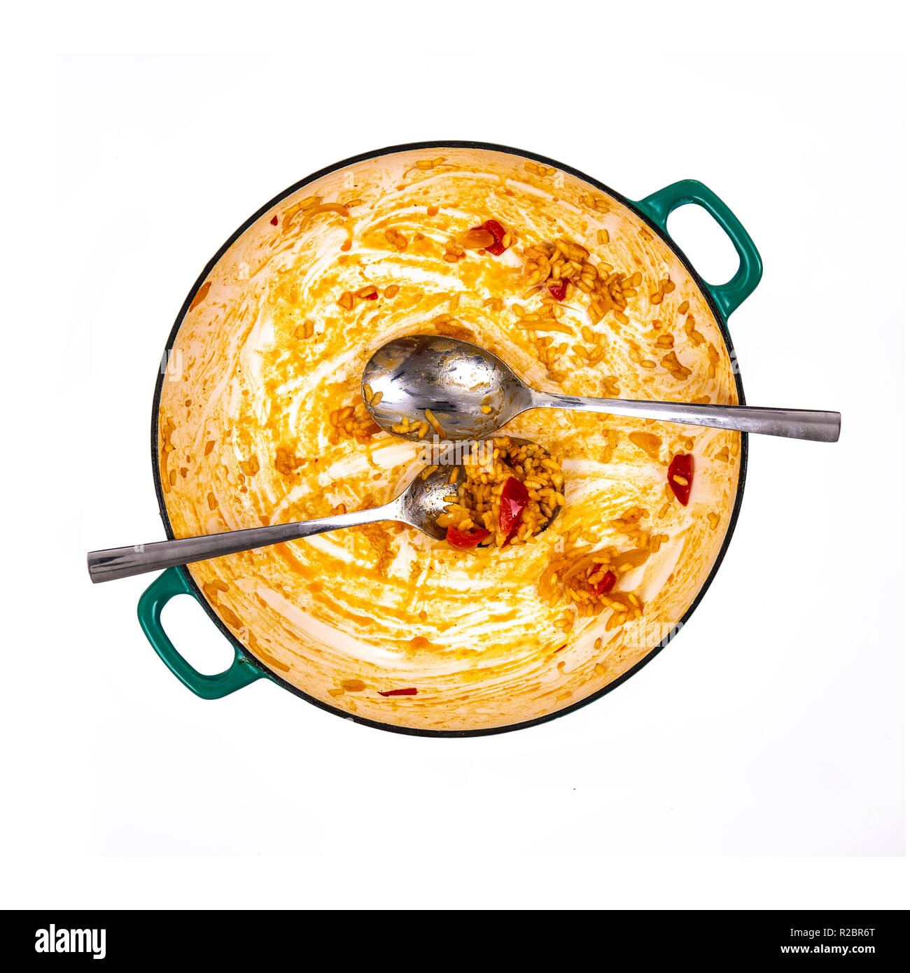 Pan of leftover Paella with spoons on a white background Stock Photo