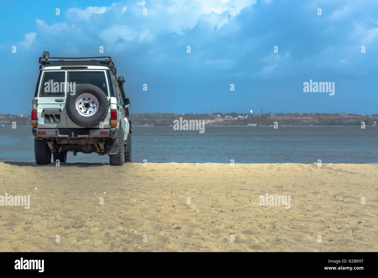 View of four-wheel drive vehicle, standing on the beach overlooking the sea, Mussulo Island, Angola - Stock Image
