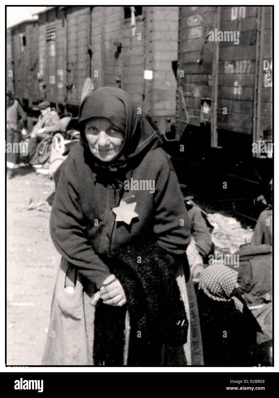 An elderly Hungarian Jewish lady, previously interned at either the Tét or Berehovo Ghetto, arrives by cattle car at Auschwitz II, also known as  Auschwitz-Birkenau. She is wearing the mandatory Nazi designated yellow star. Her haunting expression to camera is a tragic enduring image, a reminder from history of the plight and imminent unspeakable fate of her and many millions like her, whose only 'crime' was to be Jewish .... Auschwitz-Birkenau Poland - Stock Image