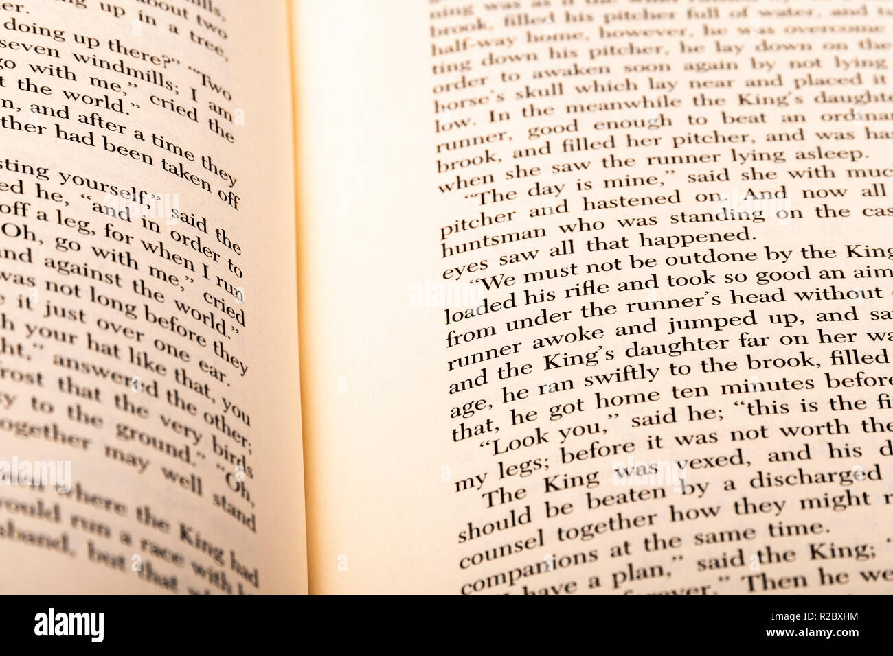 A book with English words lies open, showing portions of two pages with shallow focus and depth of field. - Stock Image