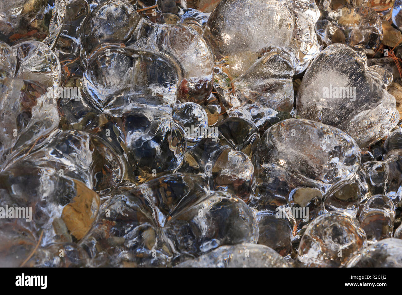 A close up abstract of ice formations from running water in winter. - Stock Image