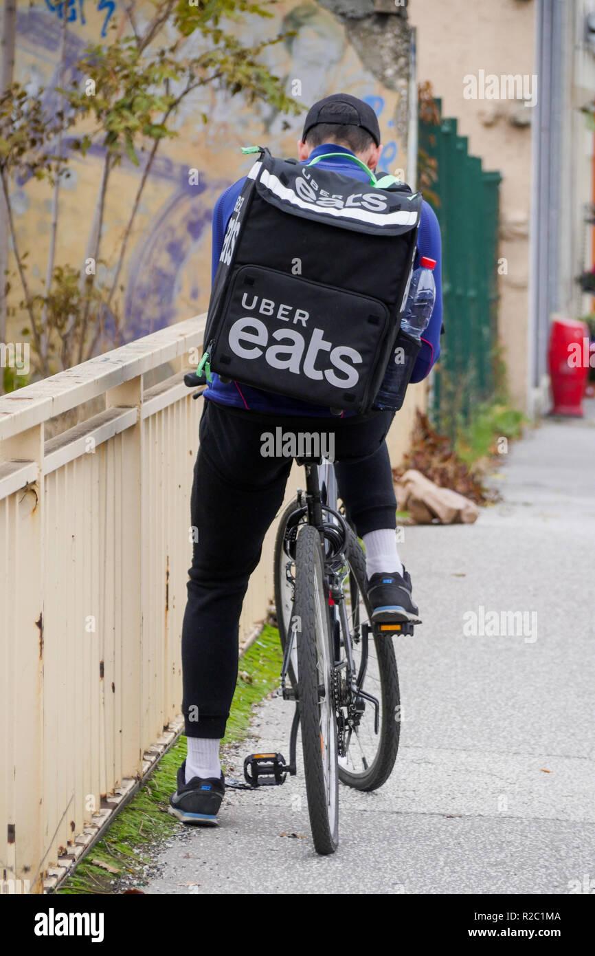 Uber Eats meal deliverer rides in Lyon, France Stock Photo