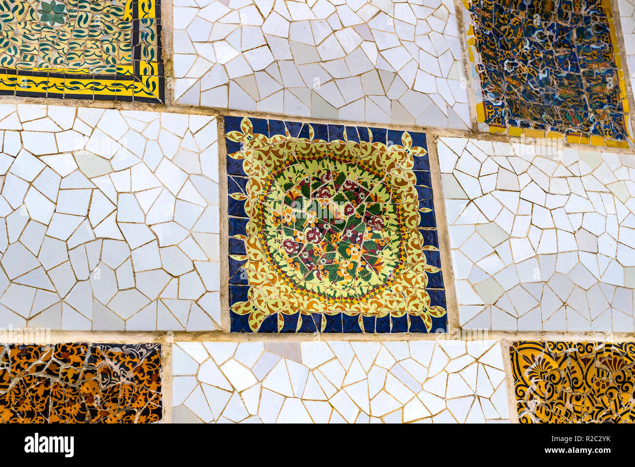 BARCELONA, SPAIN - 13 JANUARY 2018: Elements of mosaic fragments Gaudi's mosaic work in Park Guell In winter in the city of Barcelona. - Stock Image