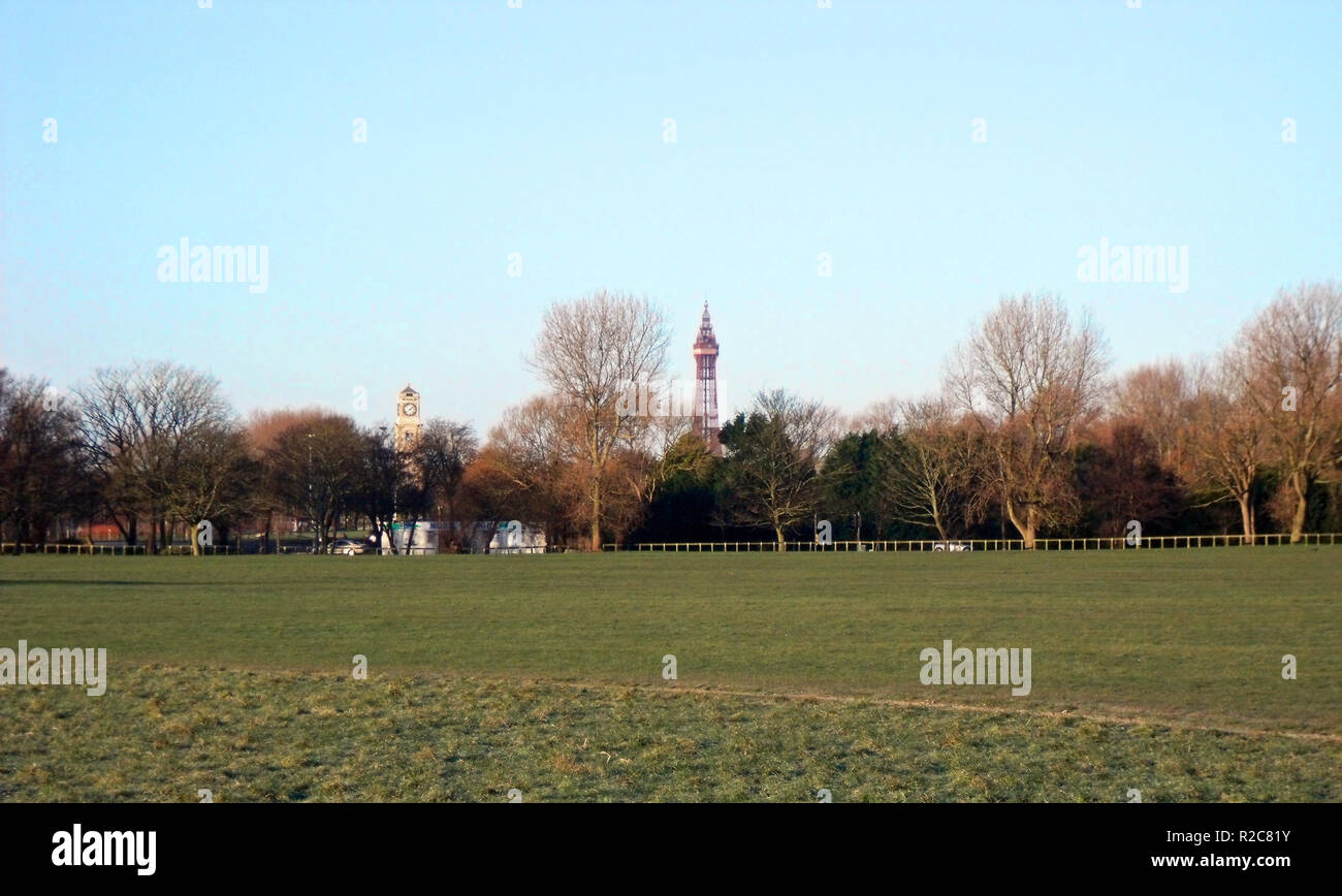 Blackpool Tower and Cocker Clock Tower in Stanley Park seen from across playing fields Blackpool Lancashire England UK Stock Photo