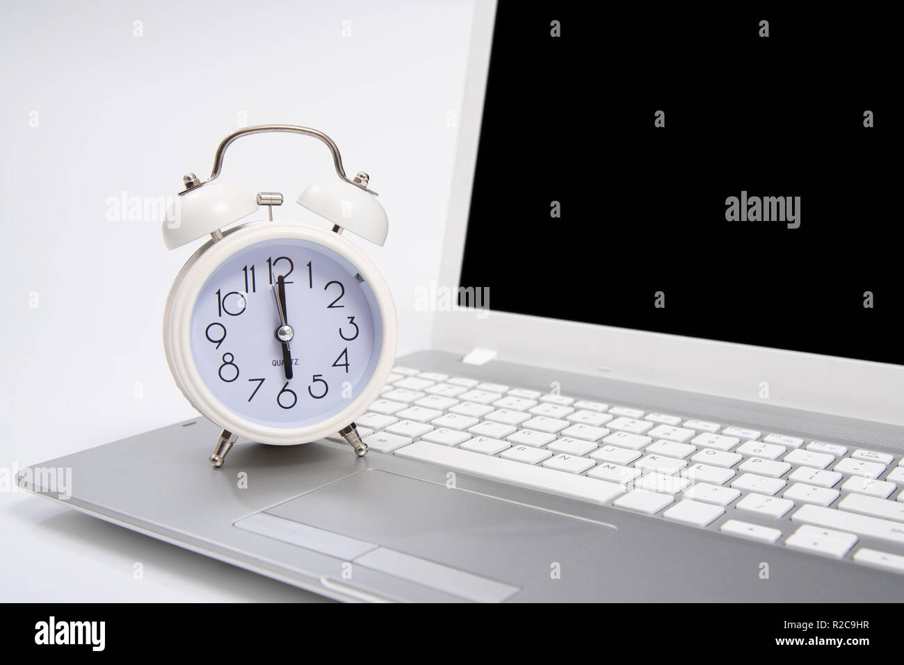 Alarm clock and portable computer put on the desk, with white background. - Stock Image
