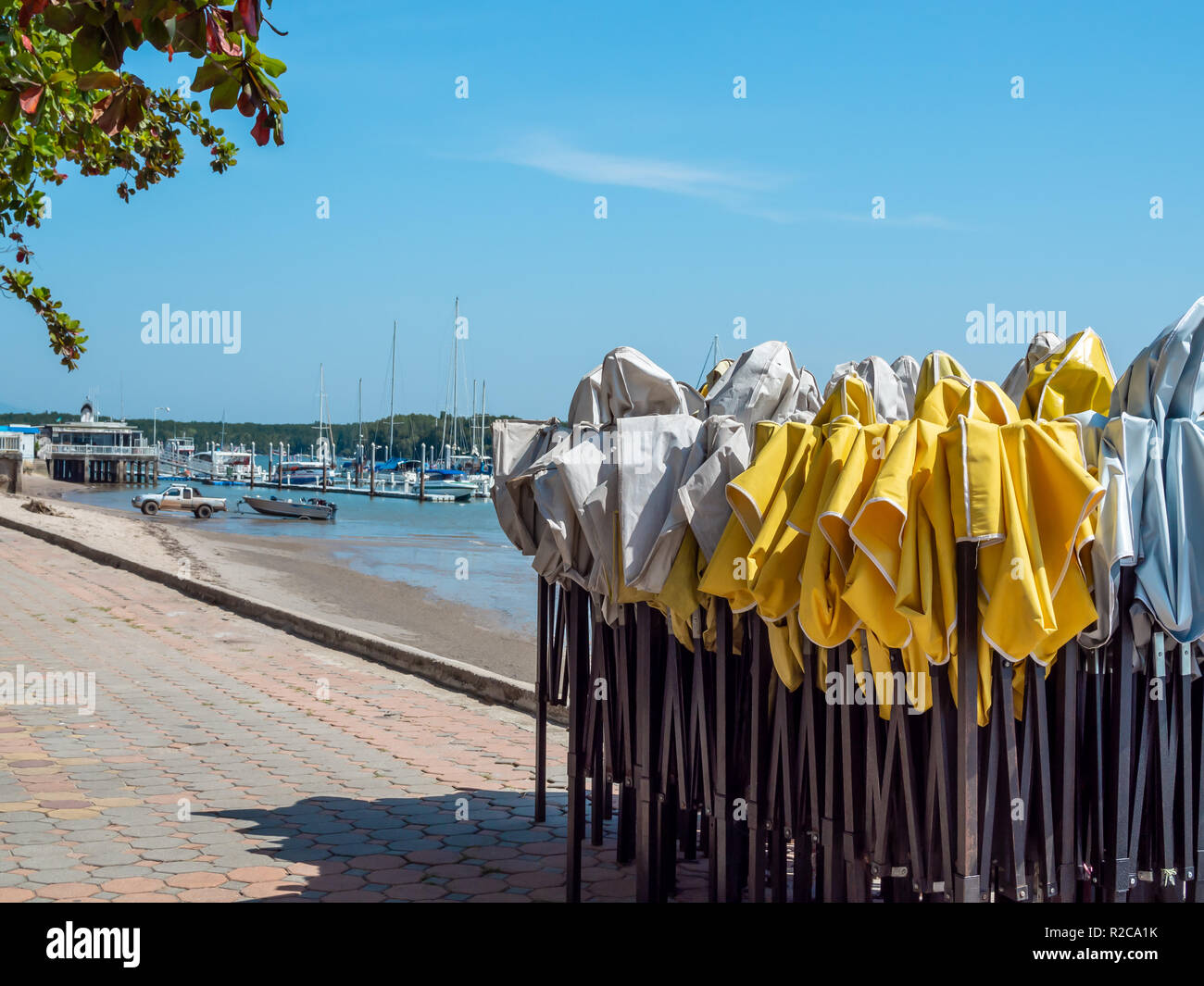 Old white and yellow outdoor folding tent standing on footpath hexagon concrete block with dirty beach background with yacht boat port on sunny day wi - Stock Image