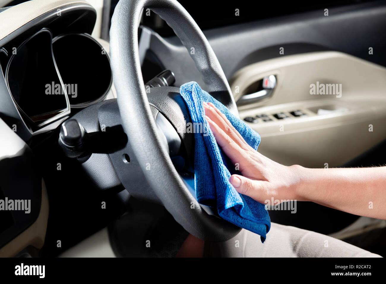 Man Using Microfiber Cloth To Cleaning Car Interior On The Garage Home