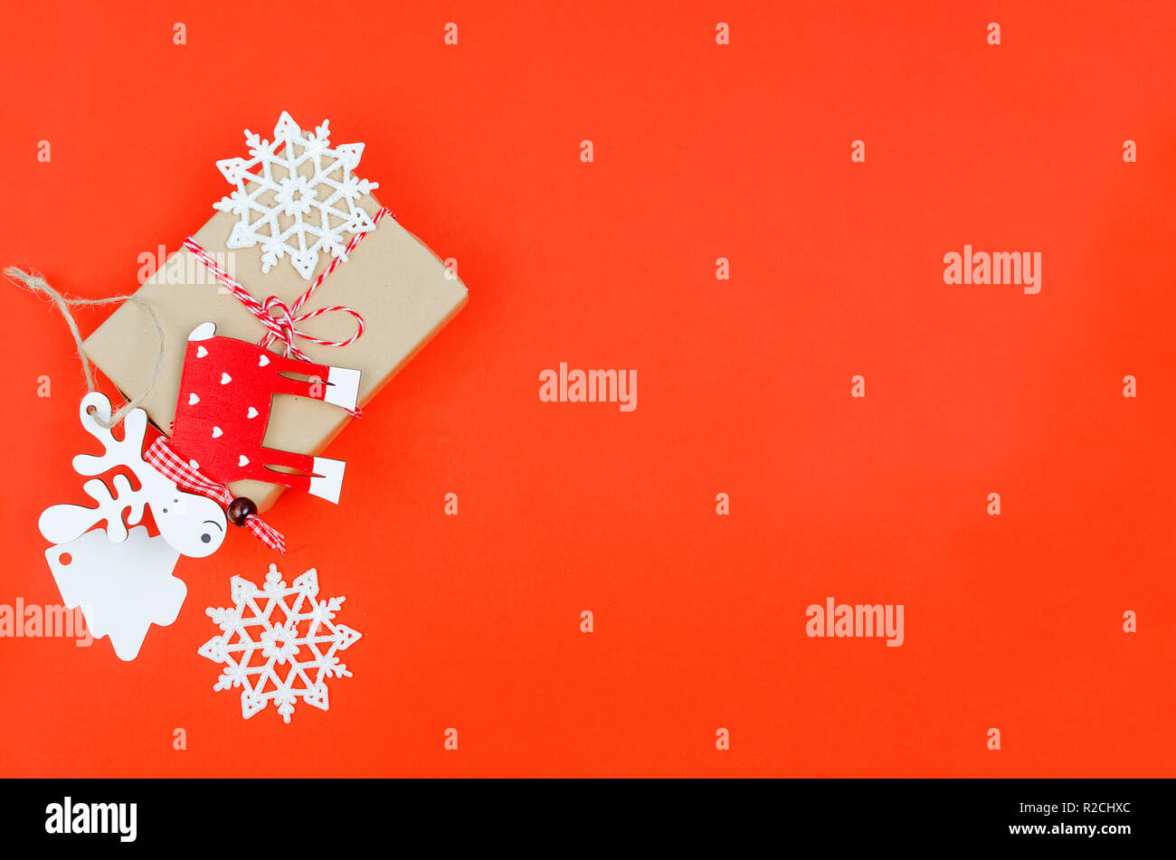 gift box with red ribbon, snowflakes and decorative toy wooden deer over the red background. top view, copy space, holiday concept, Christmas backgrou Stock Photo